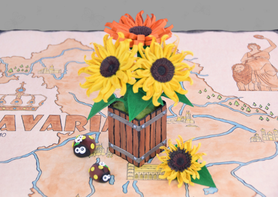 Ladybugs out of Polymer Clay. The two Beetles marching around a Sunflower arrangement. The Table decoration is on an old Map showing the Kingdom of Bavaria in 1810. The spring-like Scenery was created by Veronika Vetter and funded by Stephen Bannon
