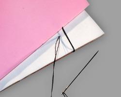 Bilder vom Binden eines Bucheinbandes mit einer Nähnadel