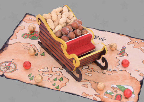 Picture of a self-made Christmas sleigh filled with Nuts. The Snow Vehicle stands on a Map of the North Pole. This Document, which was drawn by Marco Polo in the year 1312, shows where Santa Claus and his Gnomes lives